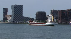 Short sea vessel passing the Headquarters of STC group, Lloyd District ROTTERDAM Stock Footage