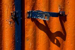 blue safety lock in a red metal wall - stock photo