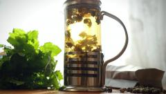 Slowmotion of glass teapot with blooming tea flower inside. Brewing tea in Stock Footage