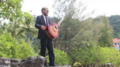Guitarist gesticulates against tropical trees Stock Footage