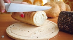 Slowmotion of Female hands cut French bread knife on a wooden board. Crumble Stock Footage