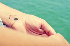 a young man with a musical note tattooed in his wrist - stock photo