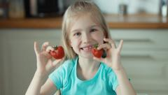 Cute girl with two strawberries dabbles and looking at camera Stock Footage