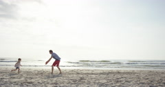 Father swinging daughter around on the beach at sunset having fun Stock Footage