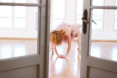 Ballerina performing a difficult position. - stock photo