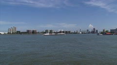 ROTTERDAM City skyline behind Nieuwe Maas, container ships cruising + pan Stock Footage