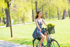 Young woman in short grey dress with long hair rides a bicycle with basket an - stock photo