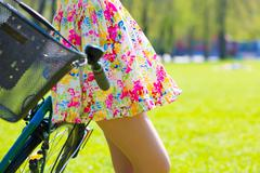 Girl in short dress with bike in summer park Stock Photos