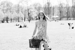 Girl in short dress with bike in summer park, black and white photo Stock Photos