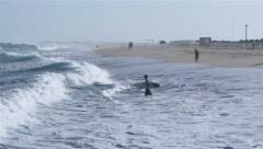 Surfer entering in waves in Tavira Island Beach Stock Footage