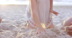 Happy family playing on the beach building sand castle at sunset Stock Footage