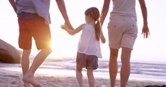 Happy family on the beach holding hands swinging little girl around at sunset on Arkistovideo