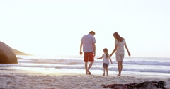 Happy family playing on the beach walking towards ocean holding hands at sunset - stock footage