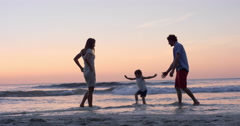 Mother swinging little girl around Happy family on the beach holding hands  at Stock Footage