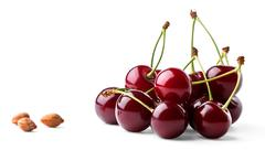 Juicy ripe cherries and cherrystones Stock Photos