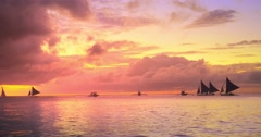 Amazing sunset sky on shore of tropical island with sail boat yachts cruising - stock footage