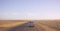 Road Trip two friends driving  in vintage convertible car on an adventure Stock Footage