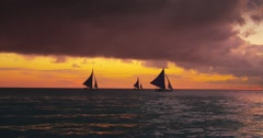 Dramatic sunset sky at sunset with sail boats on horizon - stock footage
