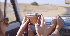 Beautiful girl taking photos with vintage camera on road trip in convertible car Stock Footage