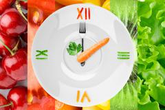Food clock with vegetables and fruits - stock photo