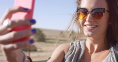 Beautiful happy woman taking selfie on road trip in convertible car Stock Footage