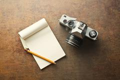 old analogue camera and notepad - stock photo