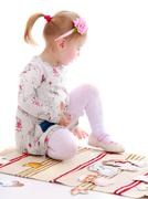 Little girl in a Montessori kindergarten playing sitting on the - stock photo