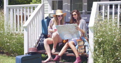 Beautiful friends planning their road trip with suitcase and map Stock Footage