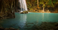 School of fish in clear water of natural pond with waterfall falling on stones Stock Footage