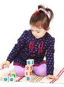 Smart little girl in a Montessori kindergarten is sitting on the - stock photo