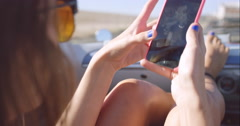 Beautiful girl taking photos with smart phone on road trip in convertible Stock Footage