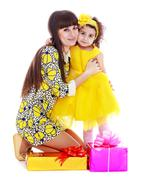 Young mother and daughter in a beautiful yellow dress Stock Photos