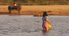 Scene of rural Myanmar at sunset. Burmese woman crossing Irrawaddy river - stock footage