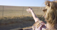 Beautiful blonde girl holding arm out of car window enjoying road trip in Stock Footage