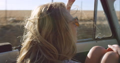beautiful blonde friend enjoying road trip in vintage convertible car - stock footage
