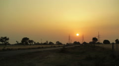 Sunset over electricity power lines, long shot, shallow DOF Stock Footage