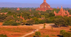 Stock Video Footage of Amazing landscape of Bagan temples and local Burmese women walk along rural road