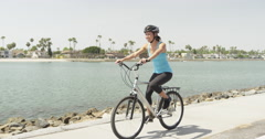 Happy young woman biking along path Stock Footage