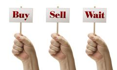 Three Signs In Fists Saying Buy, Sell and Wait - stock photo