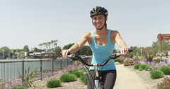 Woman smiling and biking on path Stock Footage
