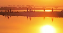 Evening sunset sky reflect in water of Irrawaddy river and young Burmese monks Stock Footage