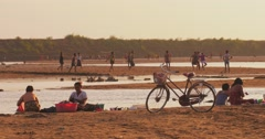 Burmese people from local village of rural Myanmar on riverbank at sunset Stock Footage
