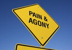 Pain and Agony Yellow Road Sign against a Deep Blue Sky with Clipping Path. - stock photo
