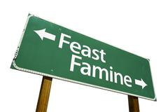 Feast Famine Green Road Sign Isolated on a White Background with Clipping Pat Stock Photos