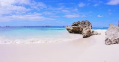 Sea coast with white sand beach and stones. Blue sky and clear water of sea Stock Footage