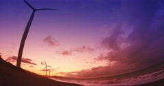 Beautiful subset in sea shore with many wind mill turbines spinning Stock Footage