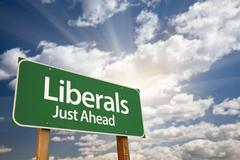Stock Photo of Liberals Green Road Sign with Dramatic Clouds, Sun Rays and Sky.