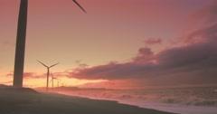 Wind mills turbines on sea coast at sunset  Stock Footage