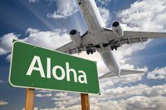 Aloha Green Road Sign and Airplane Above with Dramatic Blue Sky and Clouds. - stock photo