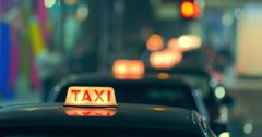 Row of taxi cabs moving on street at night in Hong Kong downtown  - stock footage